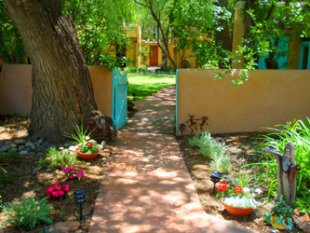 Hacienda del Sol Taos summer gardens, featuring New Mexican flowers, adobe wall garden, and turquoise gate