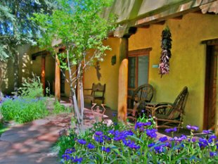 Hacienda del Sol summer gardens featuring Bachelor Buttons, Chili Ristras, and flagstone path