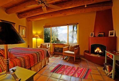 Cowgirl Room with gas log Kiva fireplace, King Silverado Coverlet, and Taos Mountain view