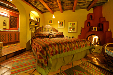 Adobe Bedroom with wood burning Kiva fireplace and Southwest decor.