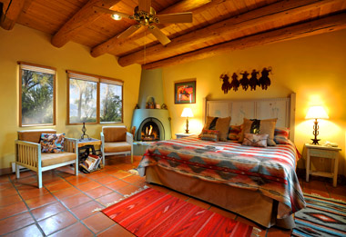 Cowboy bedroom with gas log Kiva fireplace and view of Taos Mountain