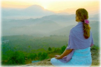 woman meditating in the mountains outdoors