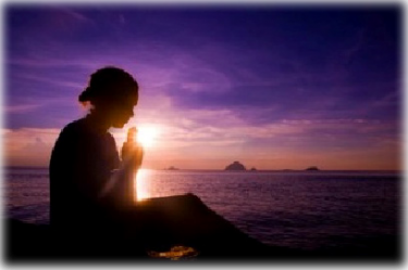 woman performing meditation and breath work next to the ocean