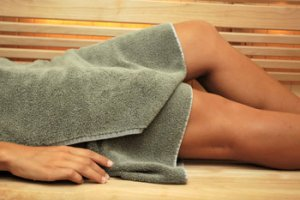 spa treatment woman with towel in sauna