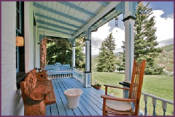bonanza room deck patio with bench and chair facing rocky mountains