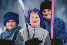 Boys holding hockey sticks for a winter activity