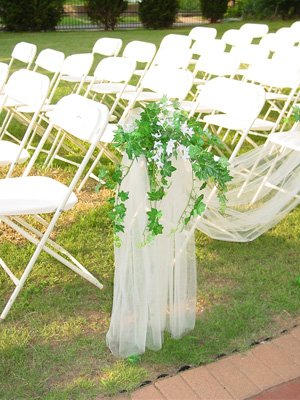 White folding chairs and aisle decorations for a wedding