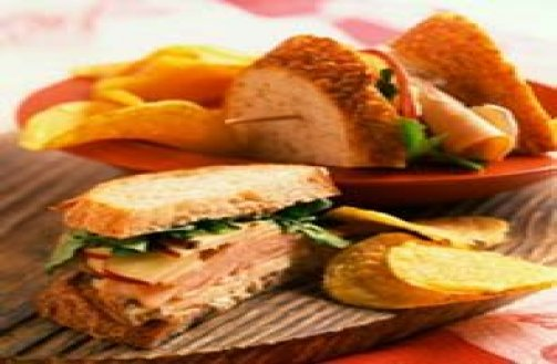 Ham and Cheese sandwich with chips and a pickle