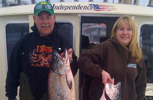 Two guests holding King Salmon from a Cook Inlet Combo trip