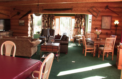 Log lodge with table, chairs, and couches