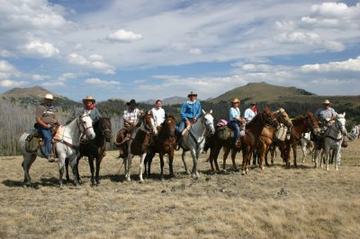 horses and riders and pack mules in yellowstone park mountains