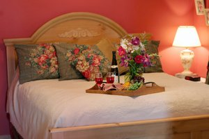 front view of bed with wine and flowers