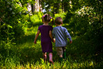 young boy and girl in forest