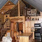 Living area with kitchen in Crazy Horse Cabin at Hochatown Junction in Broken Bow, OK