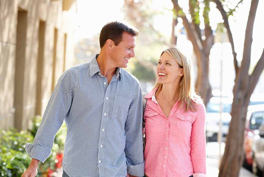 Couple smiling while walking on sidewalk
