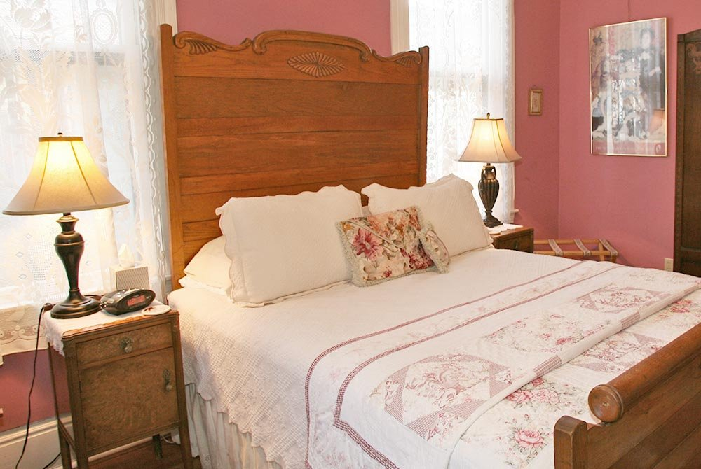 Queenbed with large headboard between windows