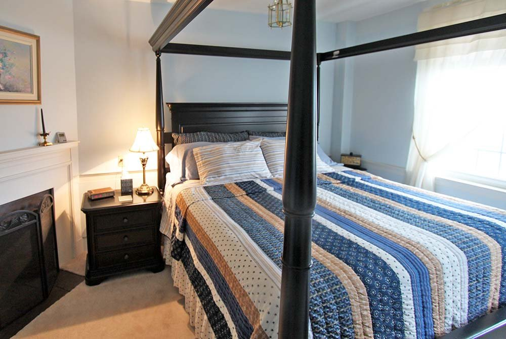Striped bedspread on a four poster bed