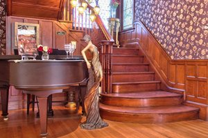 main staircase alongside piano and statue