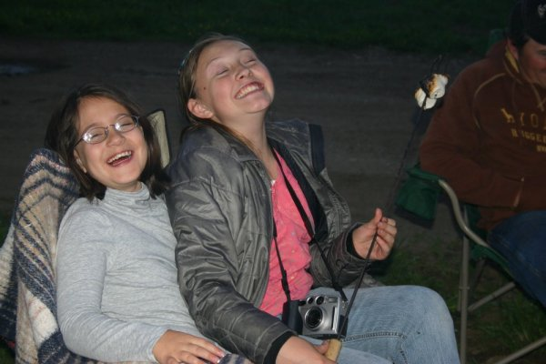 girls giggling while roasting marshmallows over campfire