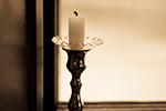 Candle in candle holder by window