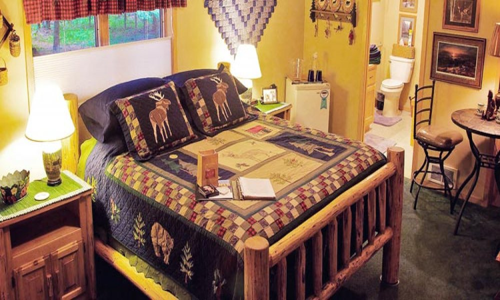 Bed with log frame with night stands, lamps, table and chairs