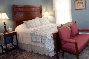 Queen bed and loveseat in bedroom