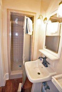Tile shower behind sink in bathroom