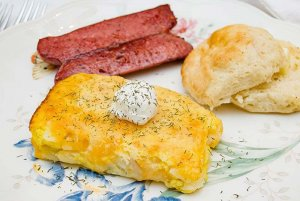 Hashbrowns, rolls, and ham on dinnerplate