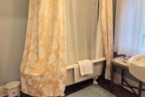 Towel hung on bathtub with shower curtain