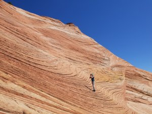 A photographer on a slope of thinly layered rock