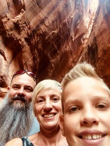 A family selfie below a narrow slot
