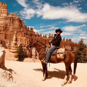 A man on horseback near delicate rock formations