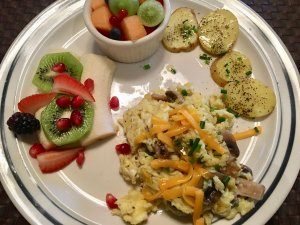 A plate of potatoes, eggs, and fresh fruit