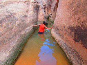 A man wading through a slot canyon