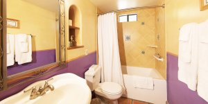 A bathroom with a purple wallpaper