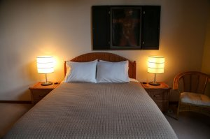 Bed with bedside lamps and art