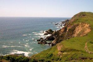 green rocky cliffs and ocean waves