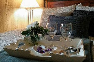 Tray of wine glasses and snacks on the bed