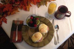 Eggs Bennedict with fruit, orange juice, and coffee in a custom mug