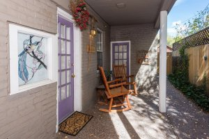 purple front door and rocking chairs