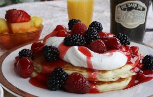 pancakes topped with whipped cream and fresh berries