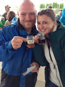 A couple holding small glasses of beer