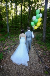 Bride and groom walking down a forest path with balloons