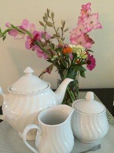 A teakettle and floral arrangement