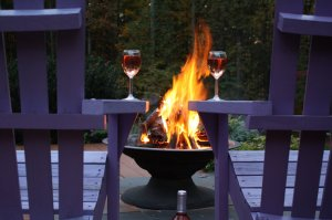 Wineglasses resting on the arms of two chairs around a firepit