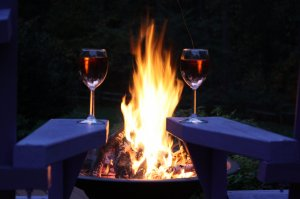 Two wineglasses on the arms of chairs around a campfire