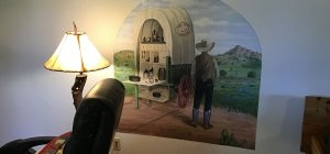 A painting of a cowboy and covered wagon