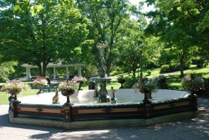 A fountain with flower planters around it