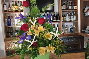 A floral arrangement on a bar with assorted drinks