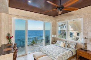 A bed adjacent to glass doors and a balcony over the ocean